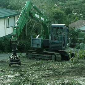 Green excavator clearing land